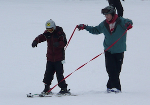 volunteer working with youth 2-track skier