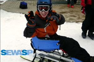 student in a bi-ski wearing a helmet & goggles