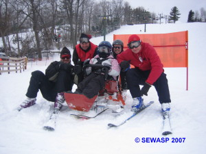 Volunteers gathered around a participant in a bi-ski